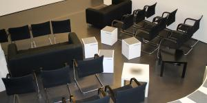 The medialounge of the zkm. Black chairs and white sitting-cubes in front of a screen.