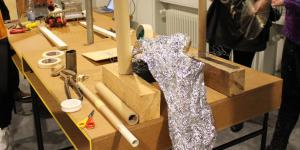 Auf einem Tisch stehen allerlei Papprollen, Klebeband und Werkzeug.