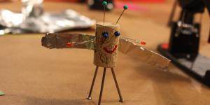 A kork, that has been turned into a little figurine with wings is sitting on a table with crafting materials around it.