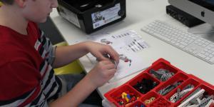Ein Junge arbeitet an einem Lego-Roboter, den er vor sich auf dem Tisch stehen hat. Um ihn herum stehen Kisten, in denen Einzelteile liegen.