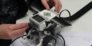 Ein Kind arbeitet an einem Lego-Roboter, gerade bringt es ein Kabel an der Vorderseite an.
