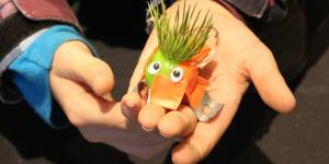 Kinderhände halten einen kleinen E-Käfer mit Kunstrasen als Haaren und Wackelaugen in die Kamera.