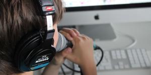 Ein Junge spricht in ein Mikrofon, das er mit beiden Händen vor den Mund hält. Er schaut dabei auf den Computerbildschirm vor ihm.