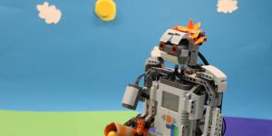 In front of a paper-set on which a sun and clouds are glued on, we can see a lego-robot.
