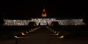 The facade of Karlsruhe´s Castle is projected with many passport photographs of various people.
