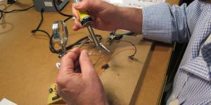 A man is soldering two wires together.