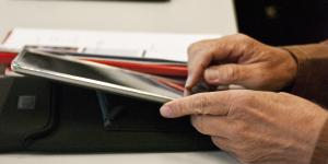 Zwei Personen sitzen am Tisch und arbeiten mit dem iPad.