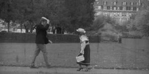 """Zwei Passanten begegnen sich auf der Straße, der Herr lüpft den Hut um die sich nähernde Dame zu grüßen. Es ist ein Standbild aus einem schwarzweiß Film, der bei dem Workshop """"Die kleinen Strolche"""" entstanden ist."""