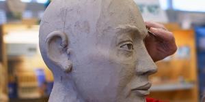 Ein Tonmodell eines Kopfes steckt auf einem Stab. Eine Frau arbeitet mit einem Modellierwerkzeug an der Augenpartie.