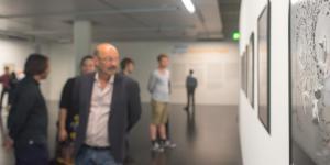 Personen im Museum bei der Ausstellungseröffnung sind nur unscharf zu erkennen. Das Bild an der Wand jedoch ist scharf und zeigt abstrakte Formen in Grautönen.