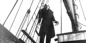 Ein Mann mit Krallenhänden steht auf einem Schiff
