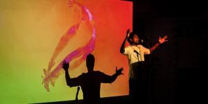 Künstler auf der Bühne, sein Schatten erscheint hinter ihm auf einer Leinwand.