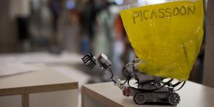 """Auf einem Tisch steht ein kleiner Lego-Roboter, an dem ein gelbes Schild mit dem Wort """"Picassoon"""" befestigt ist."""