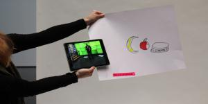 "A woman is holding a piece of paper on which a banana, an apple and a sandwich are sketched. On the bottom of the paper the word ""Allrounder"" written. Also she is holding an iPad with the photo of a man in front of a green screen."