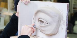 Eine Frau arbeitet an der Skulptur einer Augenpartie aus Ton. Gerade schneidet sie an der Kontur mit einem Messer ein.