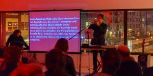A man during his performance at the keyboards, behind him a big canvas with text being screened on it.