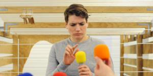 A young man taps critically with his finger on a yellow microphone. He is surrounded by different microphones.