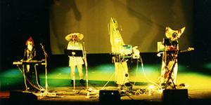 Vier Figuren stehen mit bunten Kostümen und Instrumenten auf einer Bühne