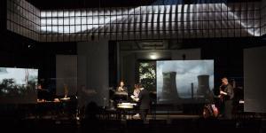 Ein Musikensemble auf einer dunklen Bühne. Im Hintergrund ein Bild von einem Atomkraftwerk