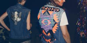 A woman and a man are standing with their backs to the observer - on their jackets there are colourful led's attached
