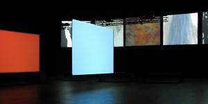 In a dark room seven screens are visible on which different abstract pictures are projected.
