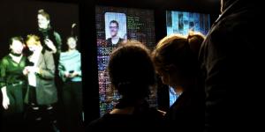 Verschiedene Personen stehen mit ihrem Smartphones vor einer Fläche mit verschiedenen digitalen Projektionen.