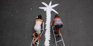 Zwei Mädchen, die auf Papier-Leitern eine Papier-Palme erklimmen