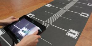 Ausschnitt eines Weges voll mit QR-Codes. Eine Hand, die mit einem iPad die QR-Codes abscannt