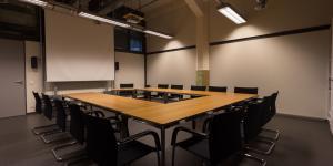 Ein Raum mit einem Tisch mit Platz für 15 Personen