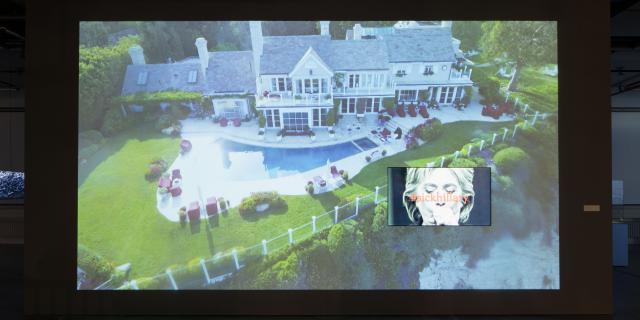 On a video screen there is a villa with pool and a picture of Hillary Clinton under which it says »sickhillary«.