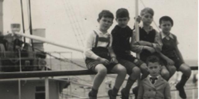 Fünf Jungen sitzen auf der Reling eines Schiffes.