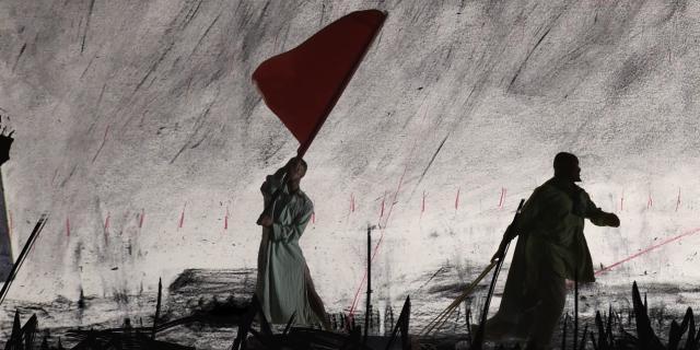 Zwei Männer, einer davon schwingt eine rote Fahne