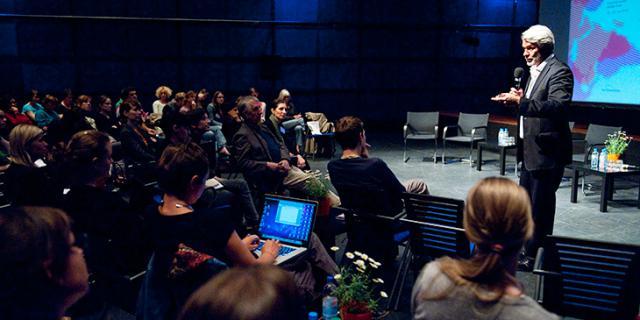 Ein Mann hält vor einem sitzenden Publikum einen Vortrag