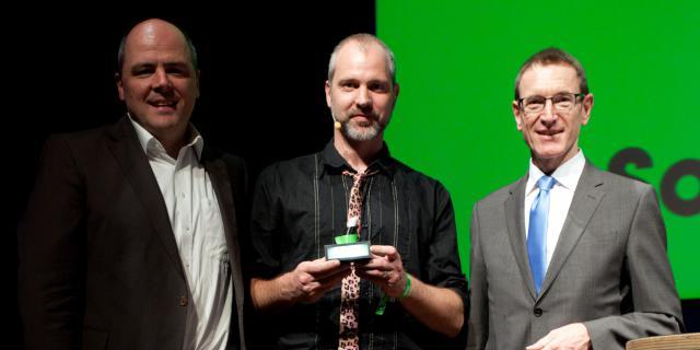 Drei Männer stehend nebeneinander von denen der mittlere einen Preis hält