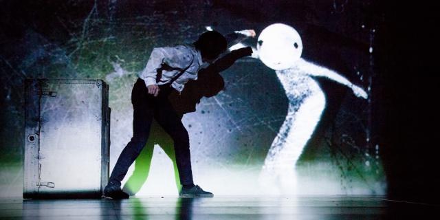 Mann auf einer Bühne kämpft gegen eine projezierte Figur