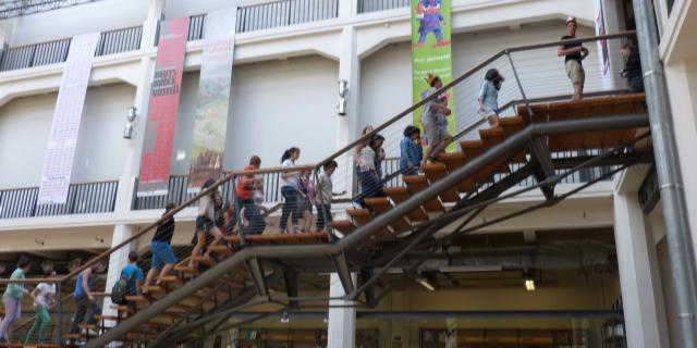 Kinder laufen die Treppe im Foyer hinauf