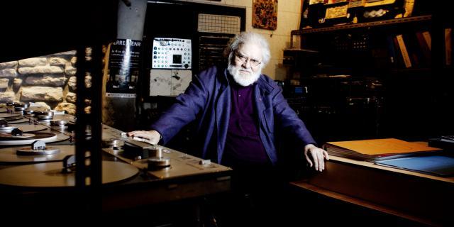 Ein Mann sitzt zwischen mehreren Plattenspielern