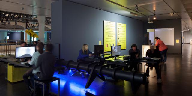 A room. Several people who play at video game consoles.