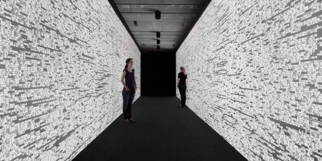 Zwei Frauen in einem Gang. Auf den Wänden sind Zahlenreihen.