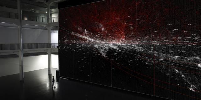 A woman in front of a huge wall, can be seen on the red and white speckles.