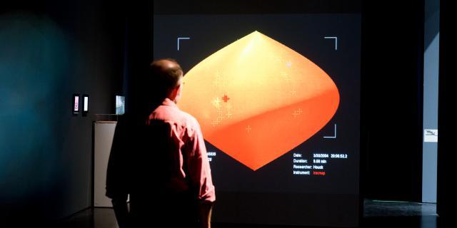 Ein Mann steht vor einer Darstellung des Raums mit einer Infrarotkamera