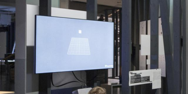Eine Junge schaut durch eine Box. An der Wand hängt ein Bildschirm mit einem Gitternetz