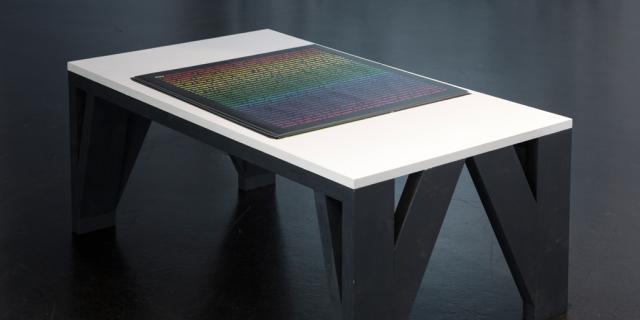 Ein Tisch, auf dem eine schwarze Kartonage mit buntem Text liegt