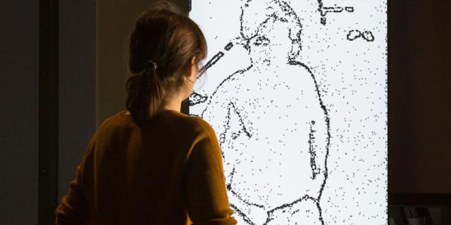 Ein Person steht vor einer Zeichnung einer Person