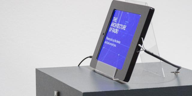 Ein Sockel, auf dem ein Tablet steht und ein Kopfhörer hängt