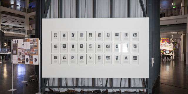 Porträts neben- und untereinander hängen an einer Wand