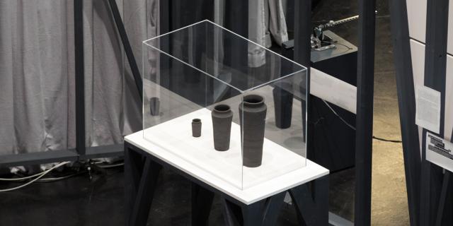 Drei verschieden große, graue Vasen in einer Vitrine