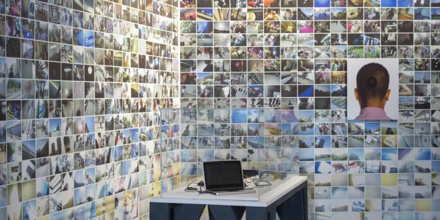 Eine Eckwand mit vielen kleinen Fotos. Im Vordergrund steht auf einem Tisch ein Laptop