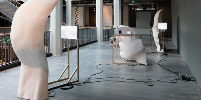 Werk bestehend aus großen weißen Köpfe mit Strukturen aus Holz und Bildschirmen