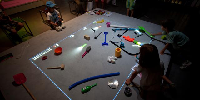Children are sitting in front of a playing area where are items lying around and virtual cars are driving